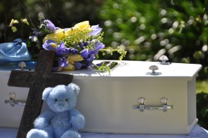 Flowers, a teddy and an iconic cross decorate Jayden's coffin